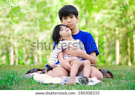 Young teen boy caring for disabled brother, looking up into sky - stock photo