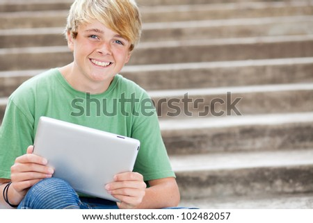 young teen boy using tablet computer - stock photo