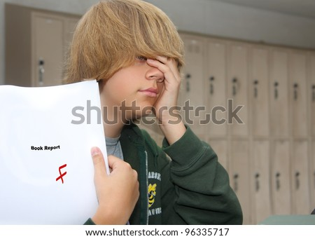 young teen boy with expression of despair upon finding a F grade on his paper. - stock photo