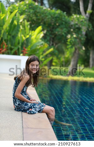 Young teen by the swimming pool. - stock photo
