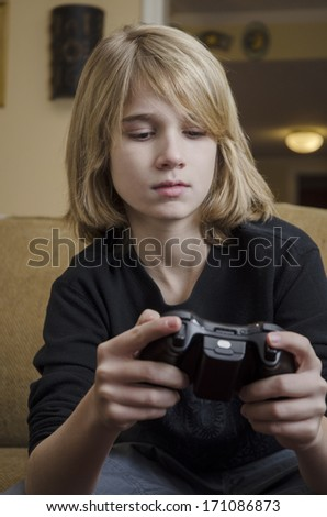Young teen concentrating on his game controller  - stock photo