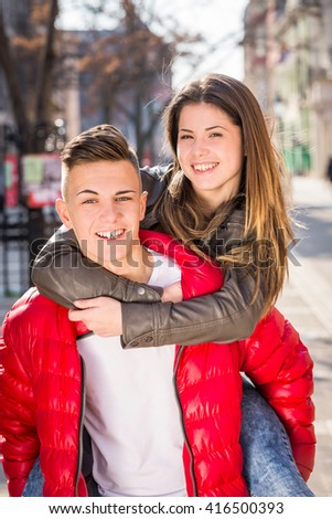 young teen couple having piggyback carrying on walking street in spring, city outdoor - stock photo