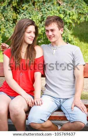 Young teen couple on a bench in city park - stock photo