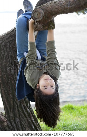 Young teen girl hanging upside down on tree limb - stock photo