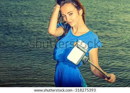 Young teen girl is making selfie (self-portrait shot) against sea water, toned image, instagram color.  - stock photo