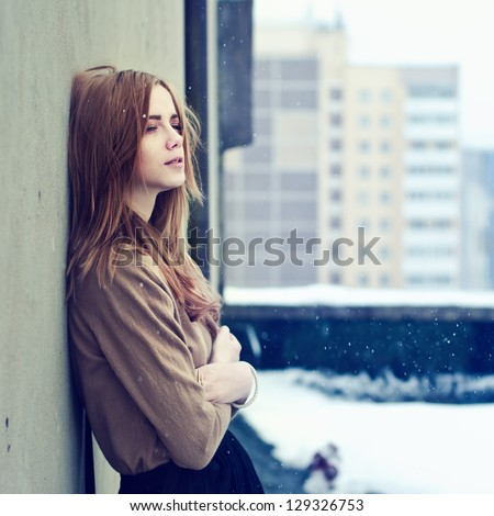 young teen girl on the roof of the winter freeze - stock photo
