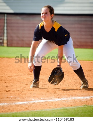 Young teen girl playing softball in organized game - stock photo