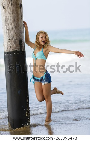 Young teen smiling and posing in jeans shorts on the beach  - stock photo