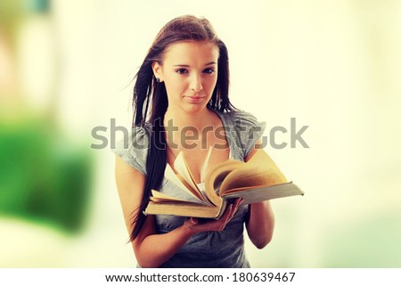 Young teen student woman reading a book  - stock photo