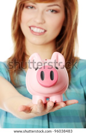 Young teen woman showing her pink piggy bank, isolated on white background - stock photo