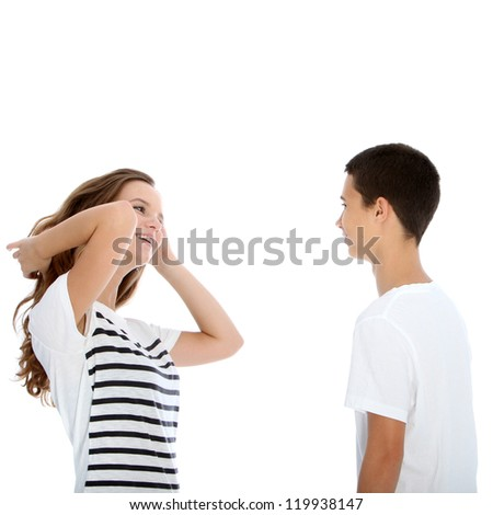 Young teenage couple talking with the girl flicking her her and laughing flirtaceously isolated on white - stock photo
