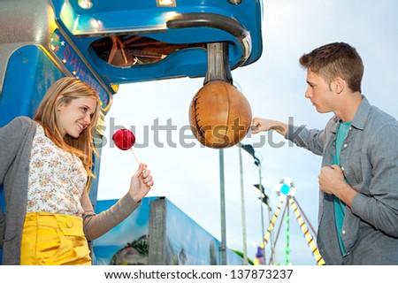 Young teenage couple visiting an attractions park arcade, playing punch boxing game during early evening with lights and rides in the background. - stock photo