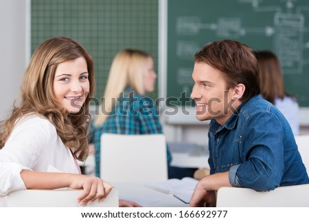Young teenage girl and boy in class at college sitting sharing a desk and turning to look back over their chairs at the camera with classmates and the blackboard behind - stock photo