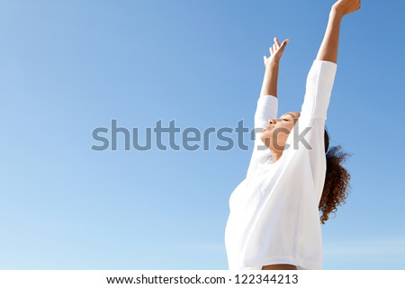 Young teenage girl breathing fresh air with her arms outstretched up and relaxing while standing against a blue sky. - stock photo