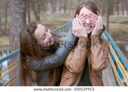 Young teenage girl closes eyes with hands to surprise her friend in park - stock photo
