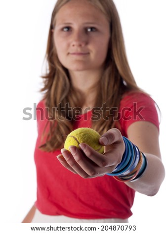 Young teenage girl holding a tennis ball in front of her over a white background - stock photo