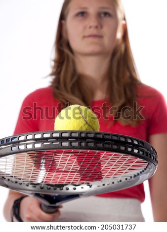 Young teenage girl holding a tennis racket and ball over a white background - stock photo