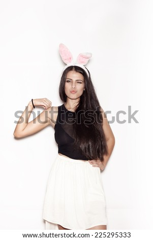 Young teenage girl in pink bunny ears. Sweet woman having fun on white background, not isolated - stock photo