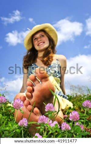 Young teenage girl sitting on summer meadow amid wildflowers in straw hat - stock photo