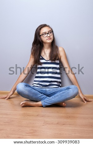 Young teenage girl sitting on the floor. Photo at home.  - stock photo