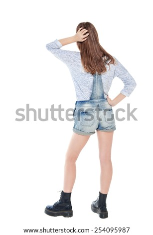 Young teenage girl standing and looking on something. Back pose, full length - stock photo