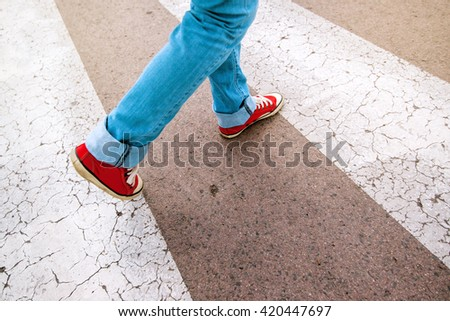 Young teenage person wearing blue jeans and red sneakers, walking over pedestrian zebra crosswalk, selective focus - stock photo