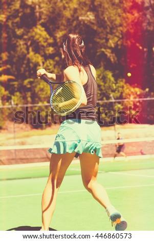 Young teenage woman playing tennis - stock photo