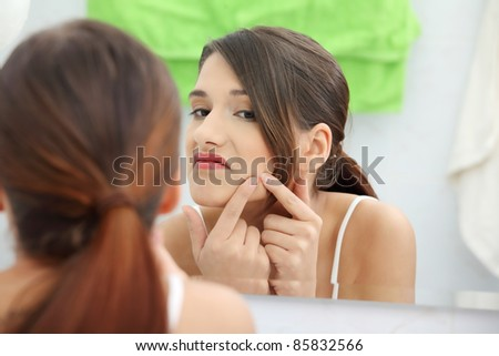 Young teenage woman with pimple on her face - stock photo