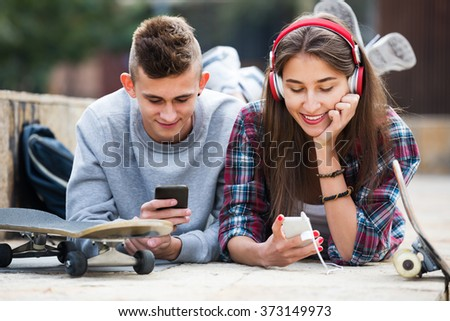 Young teenager and his happy girlfriend with smartphones outdoors  - stock photo