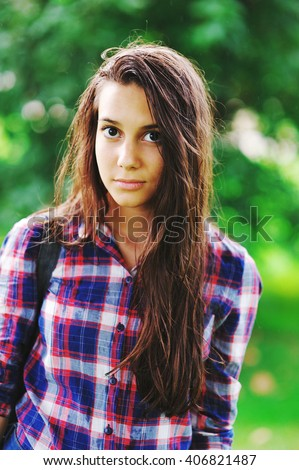 young teenager girl with wet hair from the rain in a checkered shirt looking at the camera - stock photo