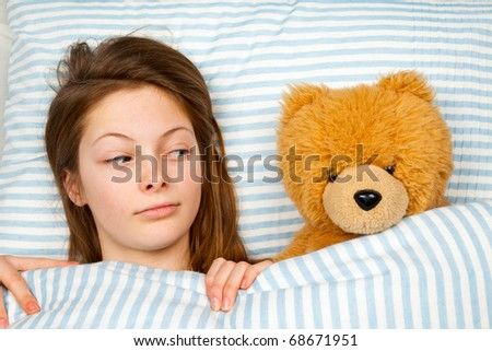 Young Teenager in Bed Looking Askance at Her Teddy Bear - stock photo