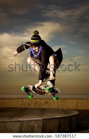 young teenager jumping with a longboard - stock photo