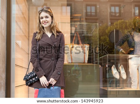 Young teenager student visiting the city during the weekend and carrying paper shopping bags while leaning on a fashion store window, smiling and being thoughtful. - stock photo