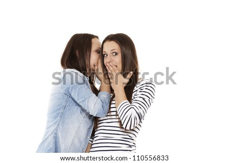 young teenager whispering at her surprised sister on white background - stock photo