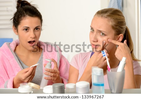 Young teenager with acne problem in the bathroom with friend - stock photo