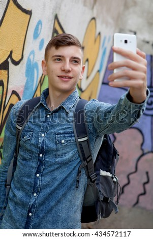Young teenager with her cell phone and near of a wall painted with graffiti - stock photo