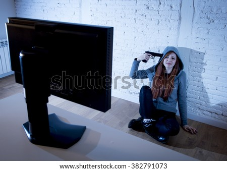 young teenager woman abused suffering internet cyberbullying scared and desperate pointing gun to her tempo in suicide gesture in front of computer monitor in cyber bullying concept - stock photo