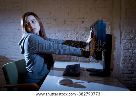 young teenager woman abused suffering internet cyberbullying scared sad and depressed in fear face expression sitting in front of computer monitor in cyber bullying social problem concept - stock photo