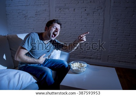 young television addict man sitting on home sofa watching TV and eating popcorn laughing crazy enjoying comedy movie or funny sitcom at night  - stock photo