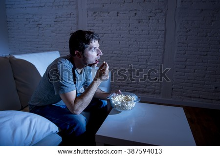 young television addict man sitting on home sofa watching TV and eating popcorn looking mesmerized enjoying movie sitcom or live sport at night  - stock photo