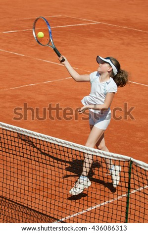Young tennis tallent hitting volley on the net. Selective focus, motion blur on racquet and ball - stock photo