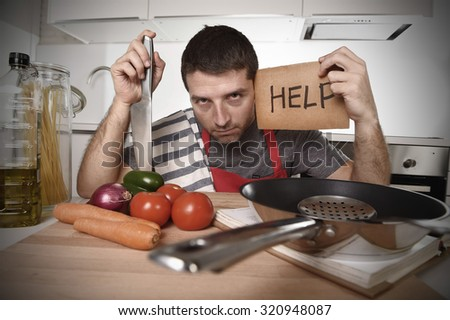 young terrified man at home kitchen wearing cook apron showing help sign looking desperate in stress holding knife with tomato in domestic mess cooking concept - stock photo