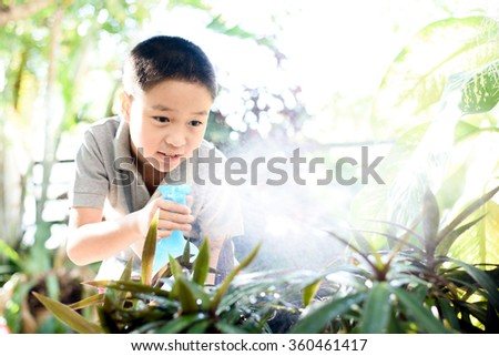 Young Thai boy spray water to the plant in his garden at home. Earth day concept. - stock photo