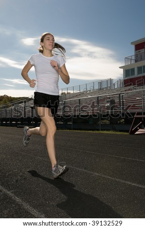 Young thin woman exercising outdoors, running on track at sports field; motion blur to represent speed - stock photo