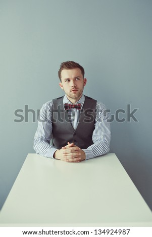 Young thinking business man sitting at the table - stock photo