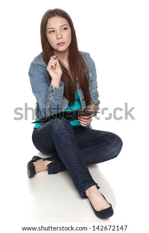 Young thinking female sitting on the floor biting the pen, looking away, in full length, isolated on white background. - stock photo