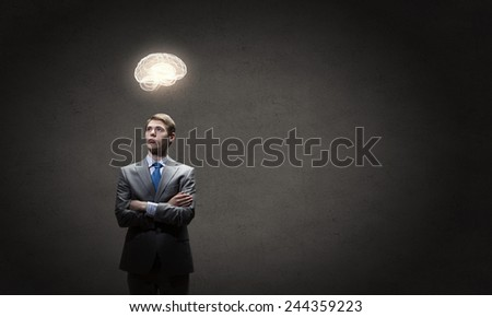 Young thoughtful businessman and human brain above his head - stock photo