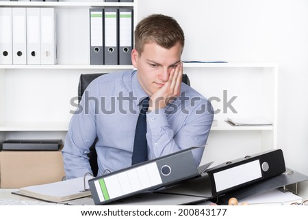 Young thoughtful businessman is sitting in front of many files on his desk in the office. A shelf is in the background. - stock photo