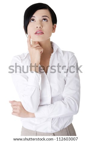 Young thoughtful businesswoman looking up - stock photo