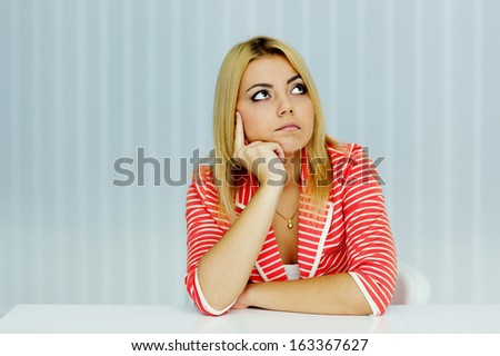 Young thoughtful woman in red jacket sitting at the table in office - stock photo